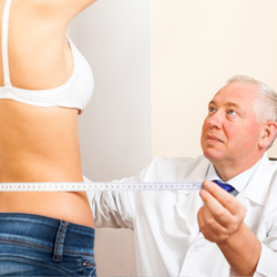 Doctor measuring the waist of a model
