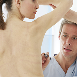 Doctor making incision marks on model's chest