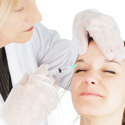Female doctor injecting a model above her right eye