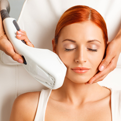 Red-headed model receiving photofacial treatment on her face