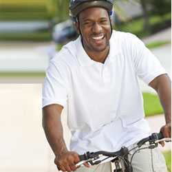 Smiling man with bike helmet riding a bike
